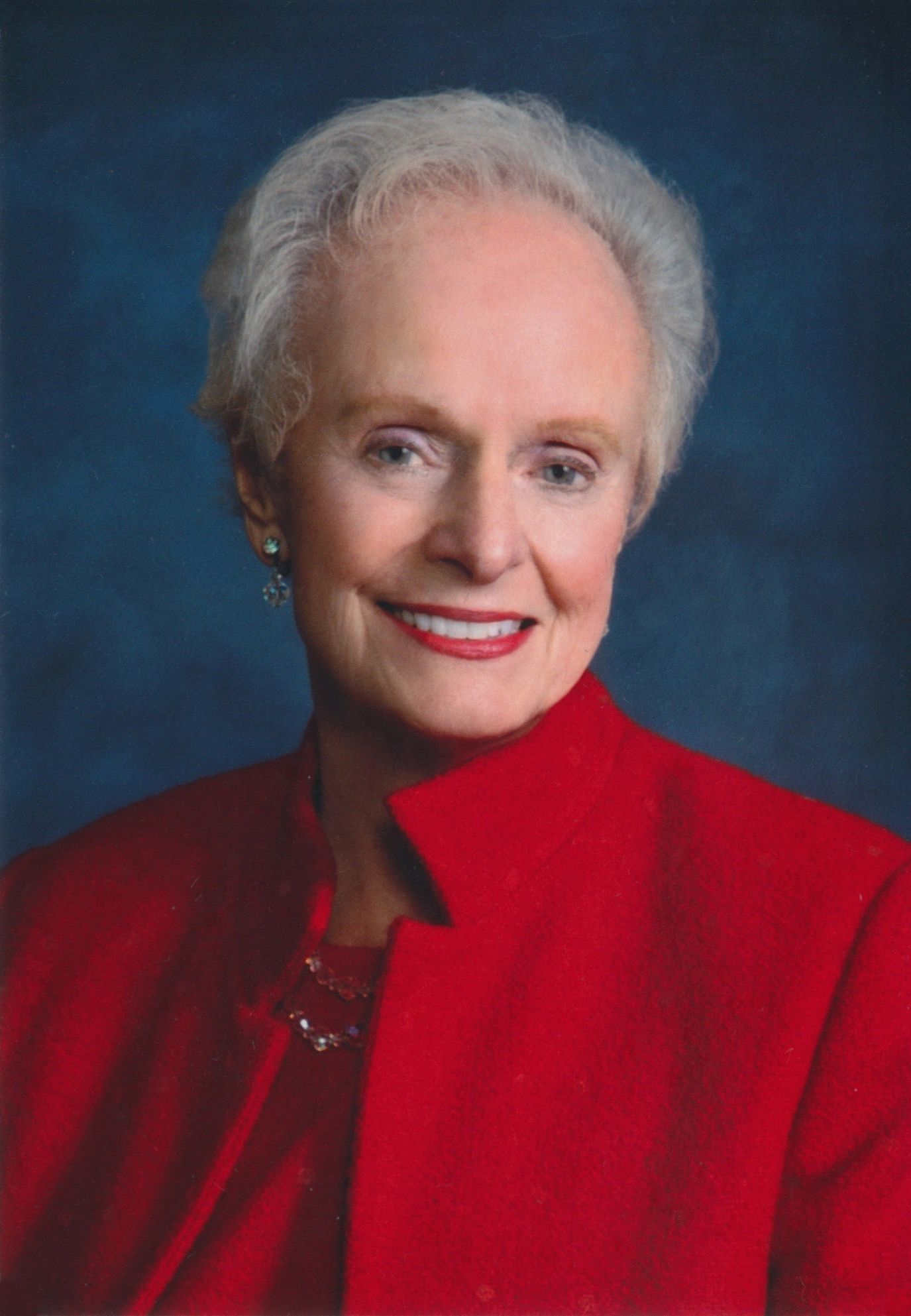 Portrait photo of Maggie Tinsman, an older white woman with white hair wearing a red coat.